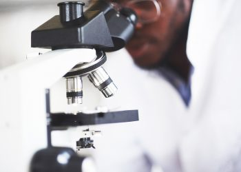 The scientist works with a microscope in a laboratory conducting experiments and formulas