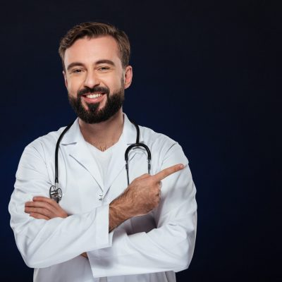 Portrait of a smiling male doctor dressed in uniform with stethoscope standing and pointing finger away at copy space isolated over dark background
